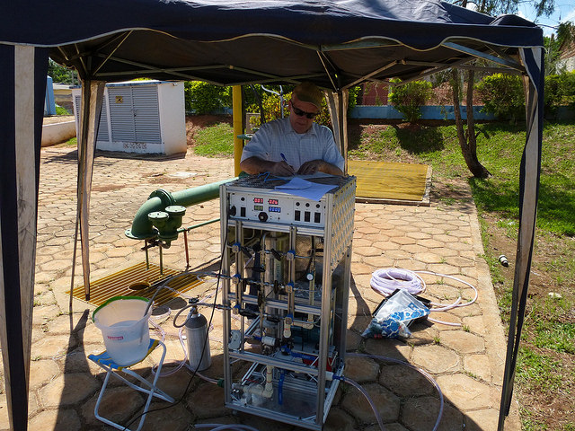 "International Atomic Energy Agency hydrologist Luis Araguas-Araguas records data as a machine extracts gases from water samples taken from the Guarani aquifer in South America. The green LED on the front panel indicates the temperature of the water (in this case, 40.9°C, or 106°F). ""Generally, the deeper the groundwater, the hotter it is,"" said Argonne scientist Wei Jiang, who coauthored a study to track helium as it moves from underground to the surface. Photo by Wei Jiang, Argonne National Laboratory."
