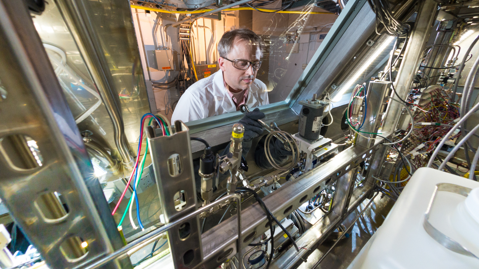 Principal chemist John Krebs performs final adjustments to an automated system designed and built by Argonne to process molybdenum-99 produced from an irradiated uranyl sulfate solution.