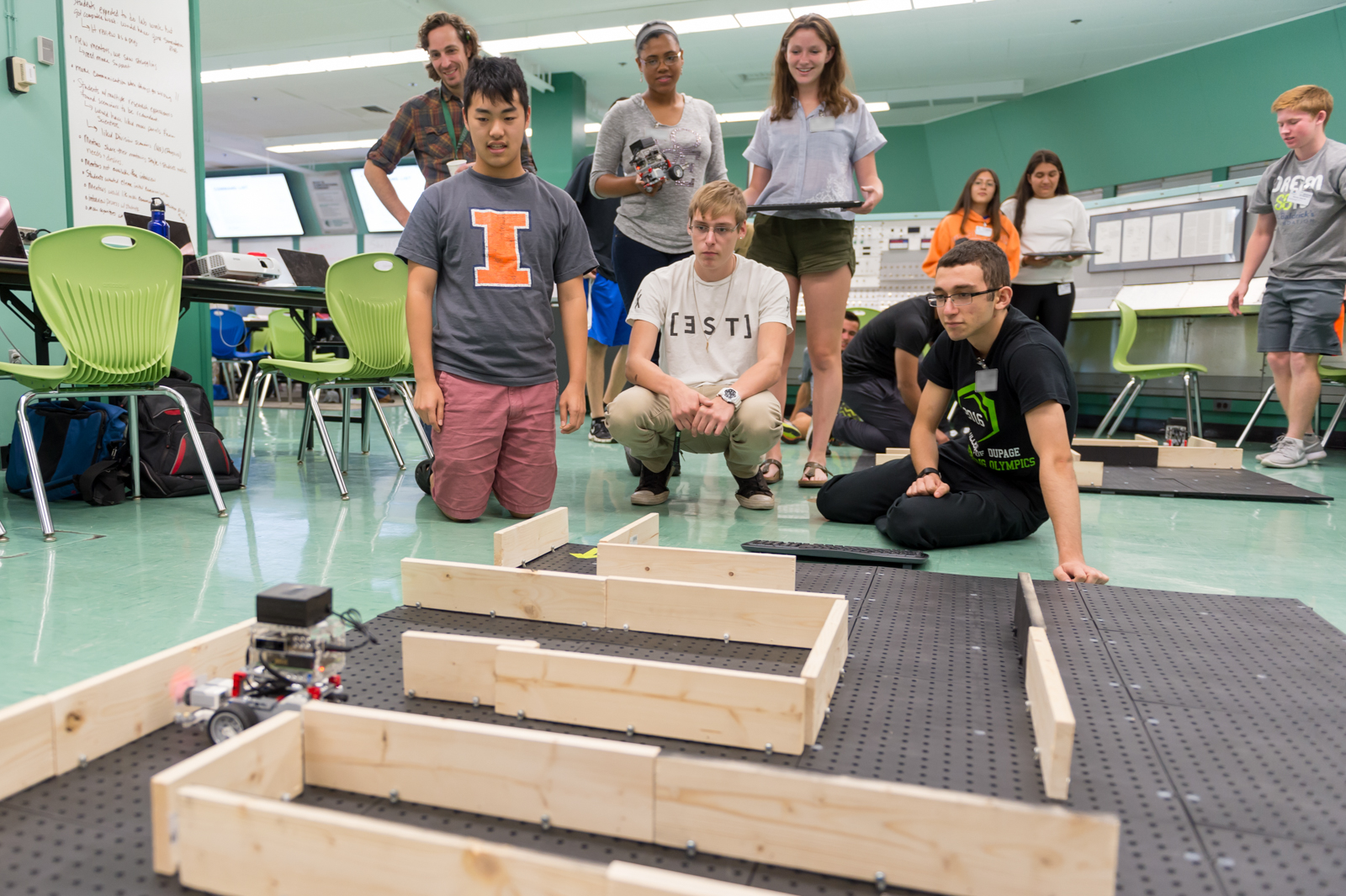 High schoolers monitor their robot's progress in the second maze on the final afternoon of camp.