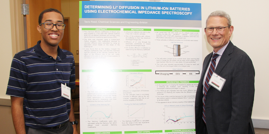 Tavis Reed presents his research about lithium-ion batteries to Argonne Interim Laboratory Director Paul Kearns.