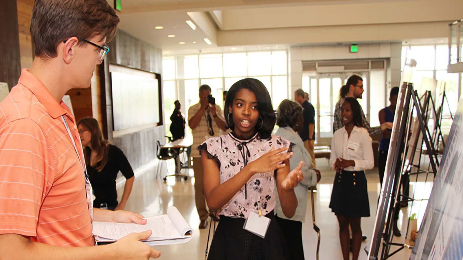Whitney Ford, a senior at Plainfield East High School, explains her award-winning research during the event to honor students and volunteers of the Argonne Afro-Academic, Cultural, Technological and Scientific Olympics (ACT-SO) High School Research Program.