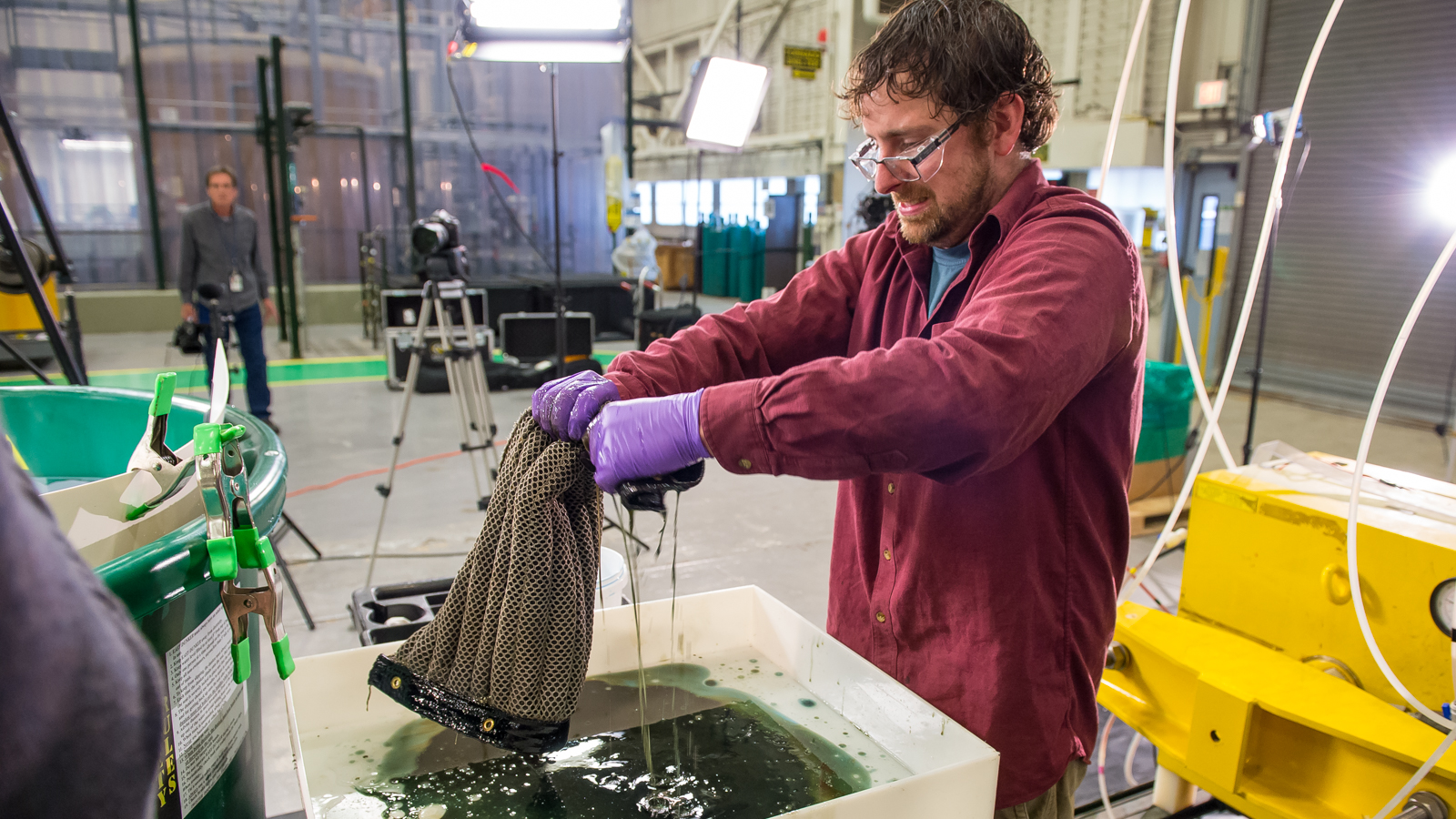 Argonne postdoctoral researcher Ed Barry wrings out a sheet of Oleo Sponge during tests at Argonne.