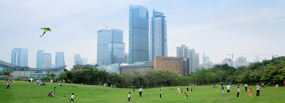 Photo of a city skyline with people enjoying a green space in the foreground.