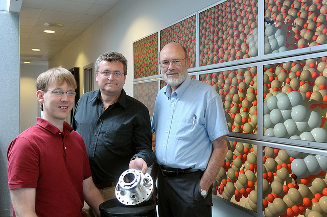 Three Argonne scientists, one of whom is holding a metallic circular instrument, stand in front of a display showing molecular structures.