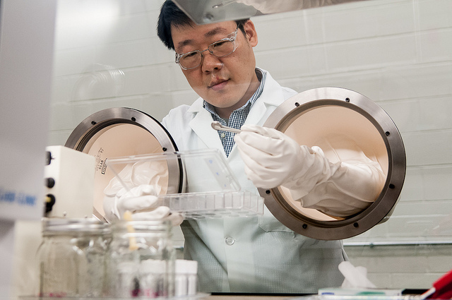 Argonne material engineer YoungHo Shin prepares a coin cell battery in a glovebox in the Materials Engineering Research Facility. Once it is prepared, the battery can be tested to determine the energy output characteristics of a cathode material for lithium-ion batteries.