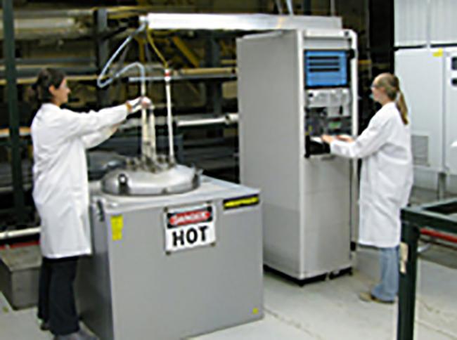 Two researchers operate Argonne's pilot-scale ultrafast boriding reactor.