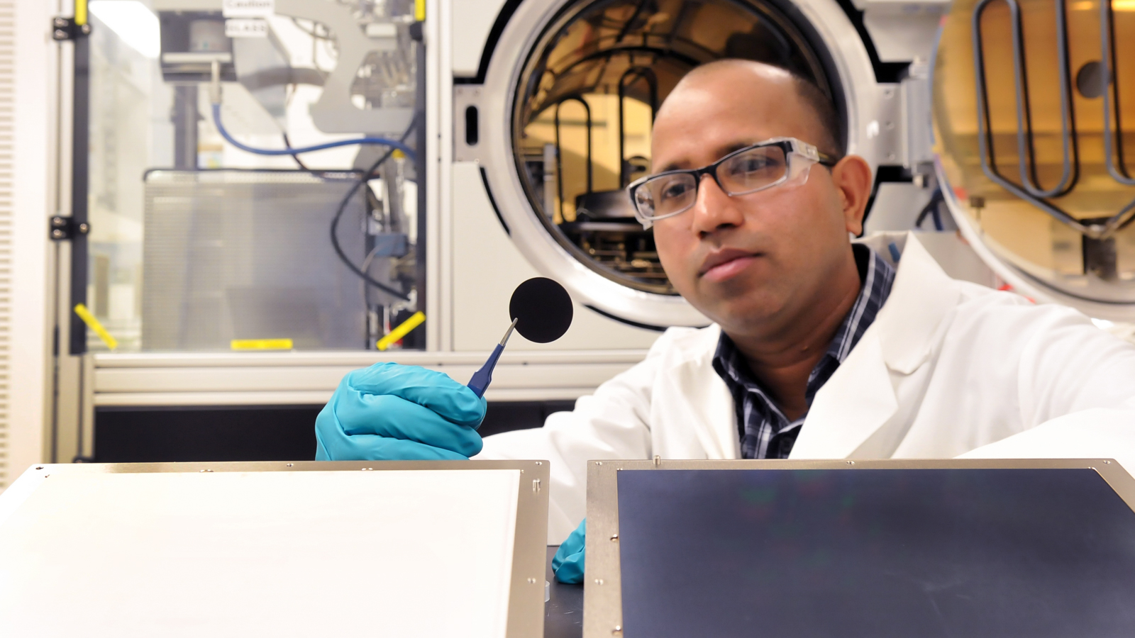 Argonne materials scientist Anil Mane examines a microchannel plate.
