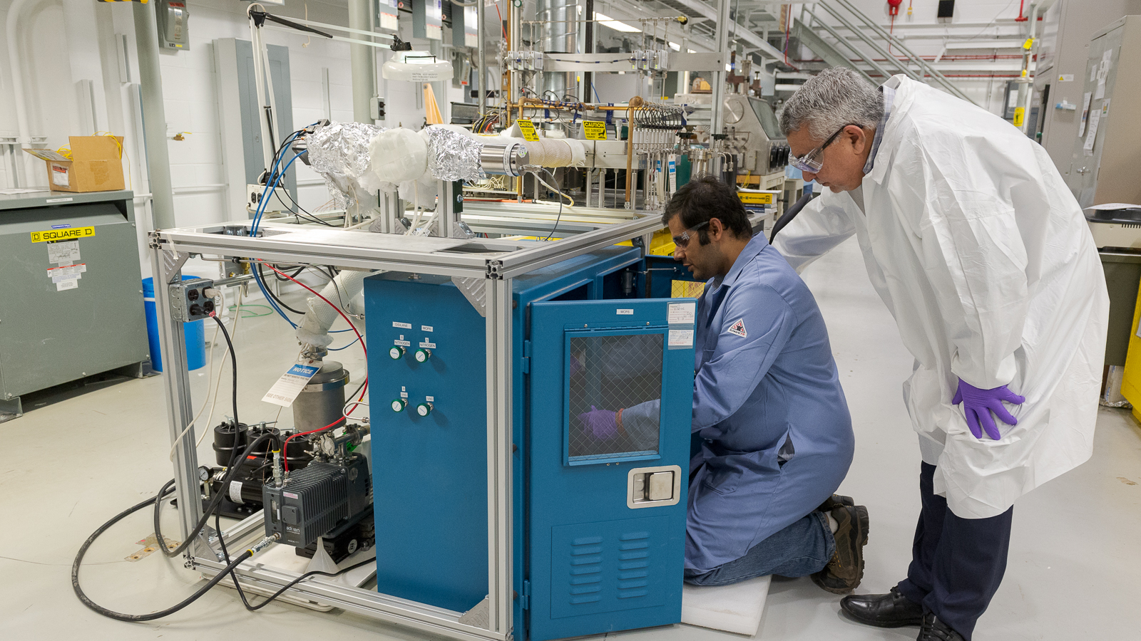 Here, Bhattacharya and Yacout adjust lab equipment to deposit ALD-based nuclear coatings. (Image by Argonne National Laboratory.)