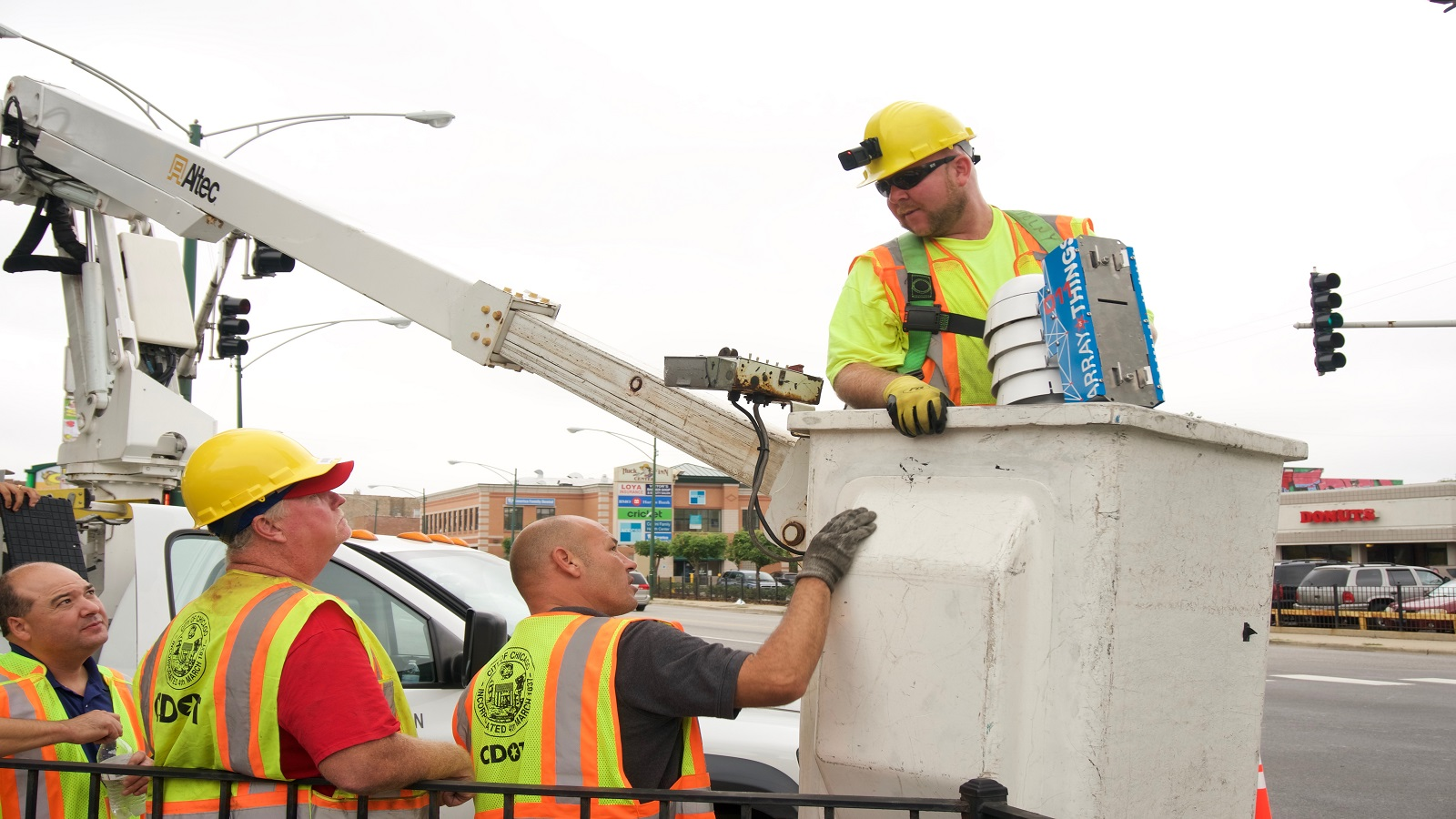 Workers from the Chicago Department of Transportation install a node for the Array of Things, a distributed sensing network for urban environments, at Damen and Archer avenues in downtown Chicago. (Image by Rob Mitchum/University of Chicago.)