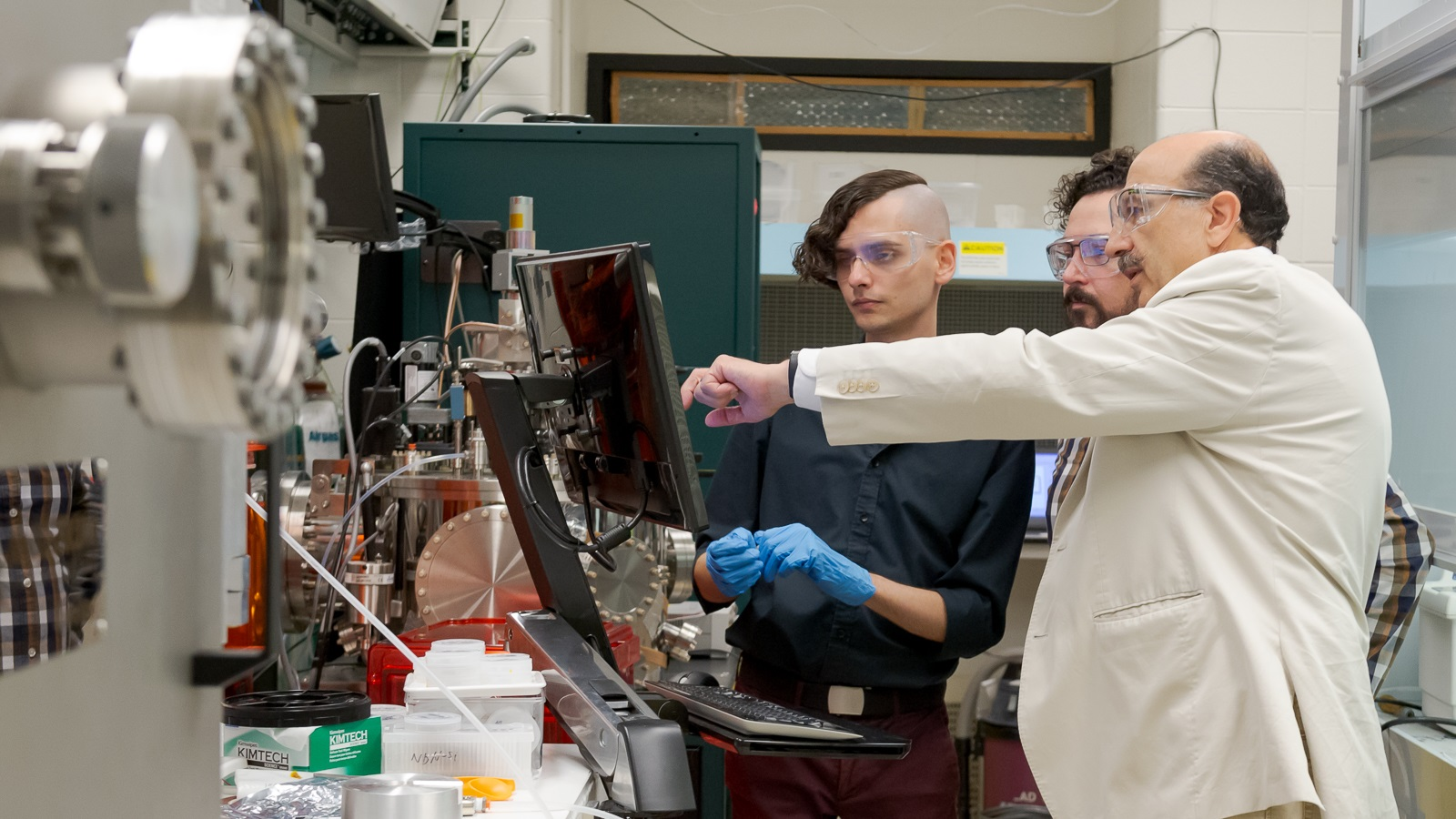 Argonne scientists at nanowire fabrication machine. Left to right: T. Polakovic, W.R. Armstrong and Z.-E. Meziani. (Image by Argonne National Laboratory.)