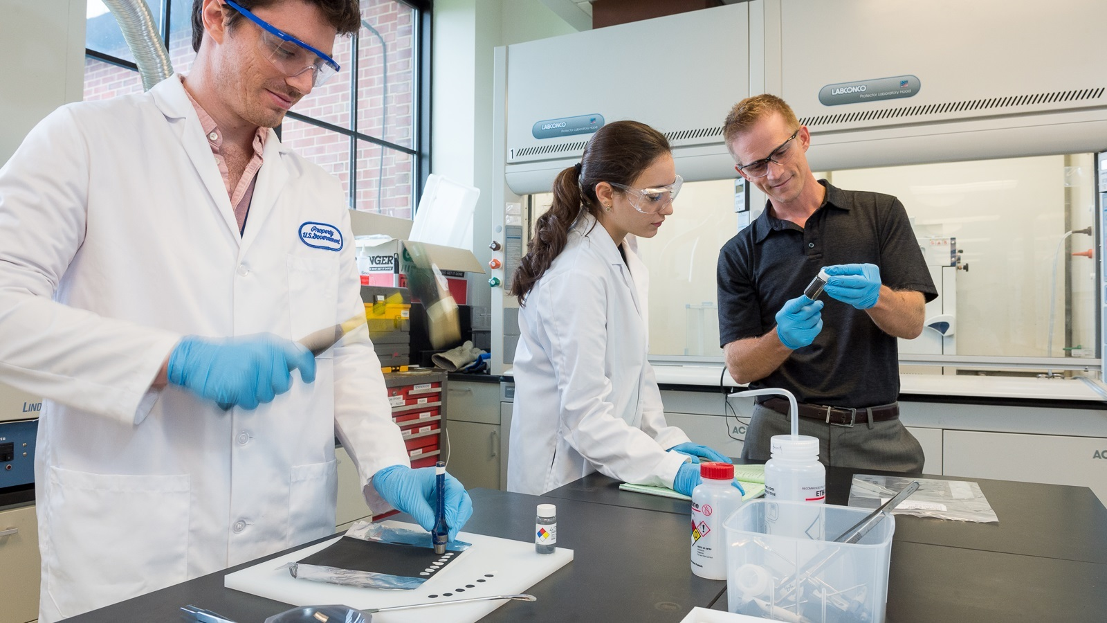 Argonne scientists Jason Croy, Manar Ishwait and Michael Murphy assemble lithium-ion battery electrodes for testing. (Image by Mark Lopez / Argonne National Laboratory.)