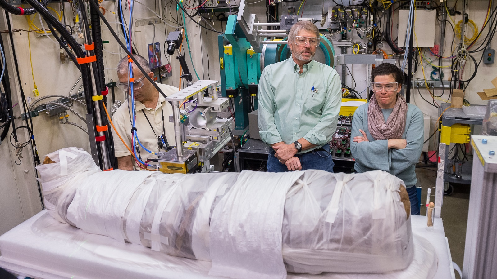 Stuart Stock, center, of Northwestern University, talks with Rachel Sabino, right, of the Art Institute of Chicago in 2017 while Argonne scientist Ali Mashayekhi, left, makes adjustments to the apparatus holding a 1,900-year-old Egyptian mummy. (Image by Mark Lopez / Argonne National Laboratory.)