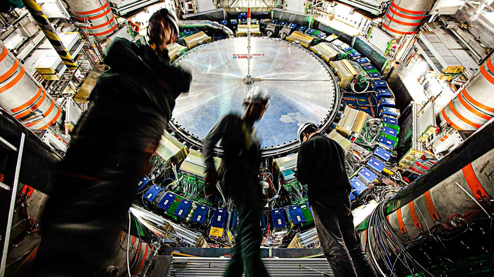 Workers inside ATLAS, one of several primary detectors for the Large Hadron Collider at CERN. ATLAS witnesses a billion particle interactions every second and the signatures of new particles created in near-speed-of-light proton-proton collisions. (Image by CERN.)