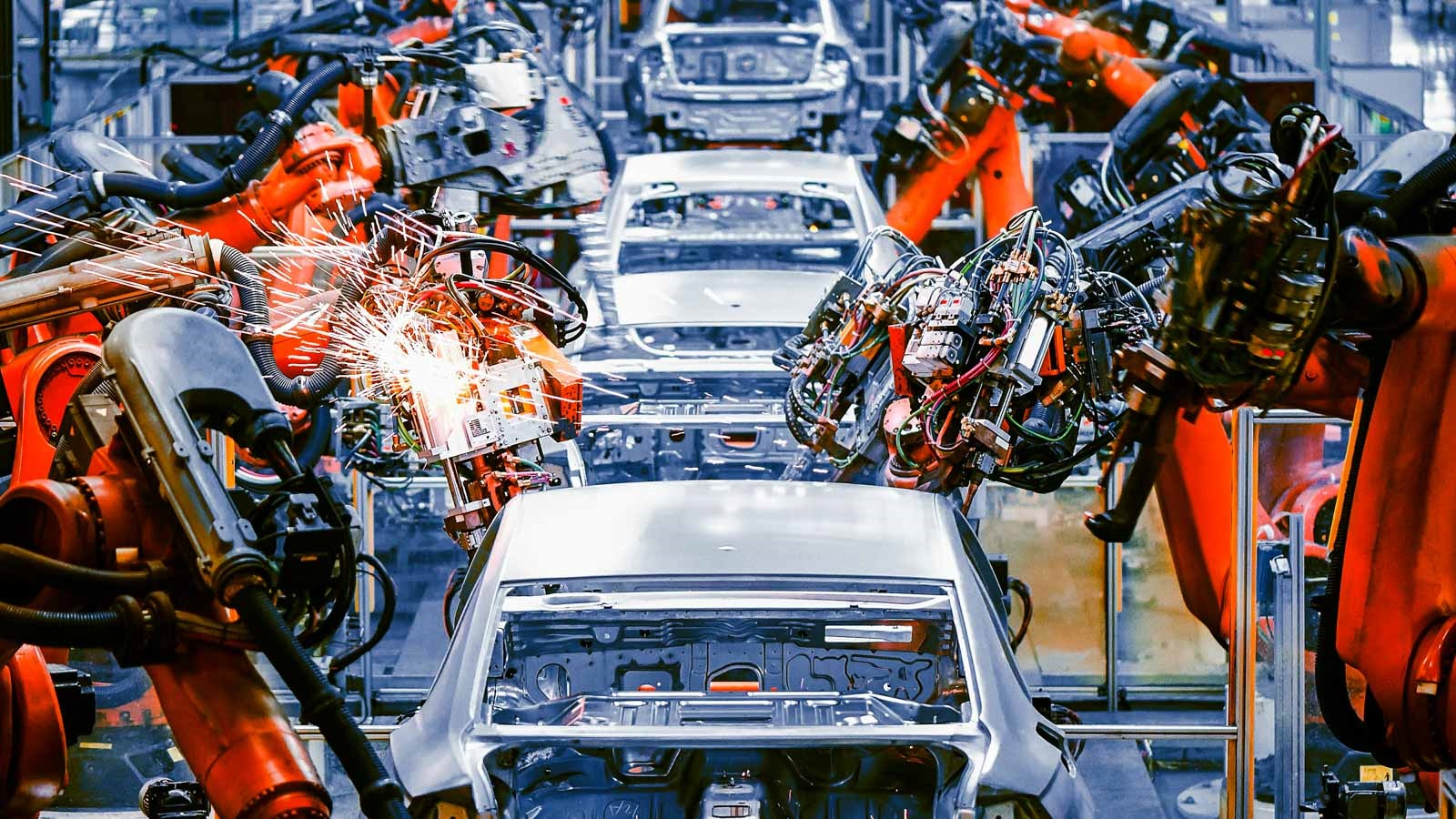 Line of cars being worked on by robotic arms. (Image by Shutterstock/Jensen.)