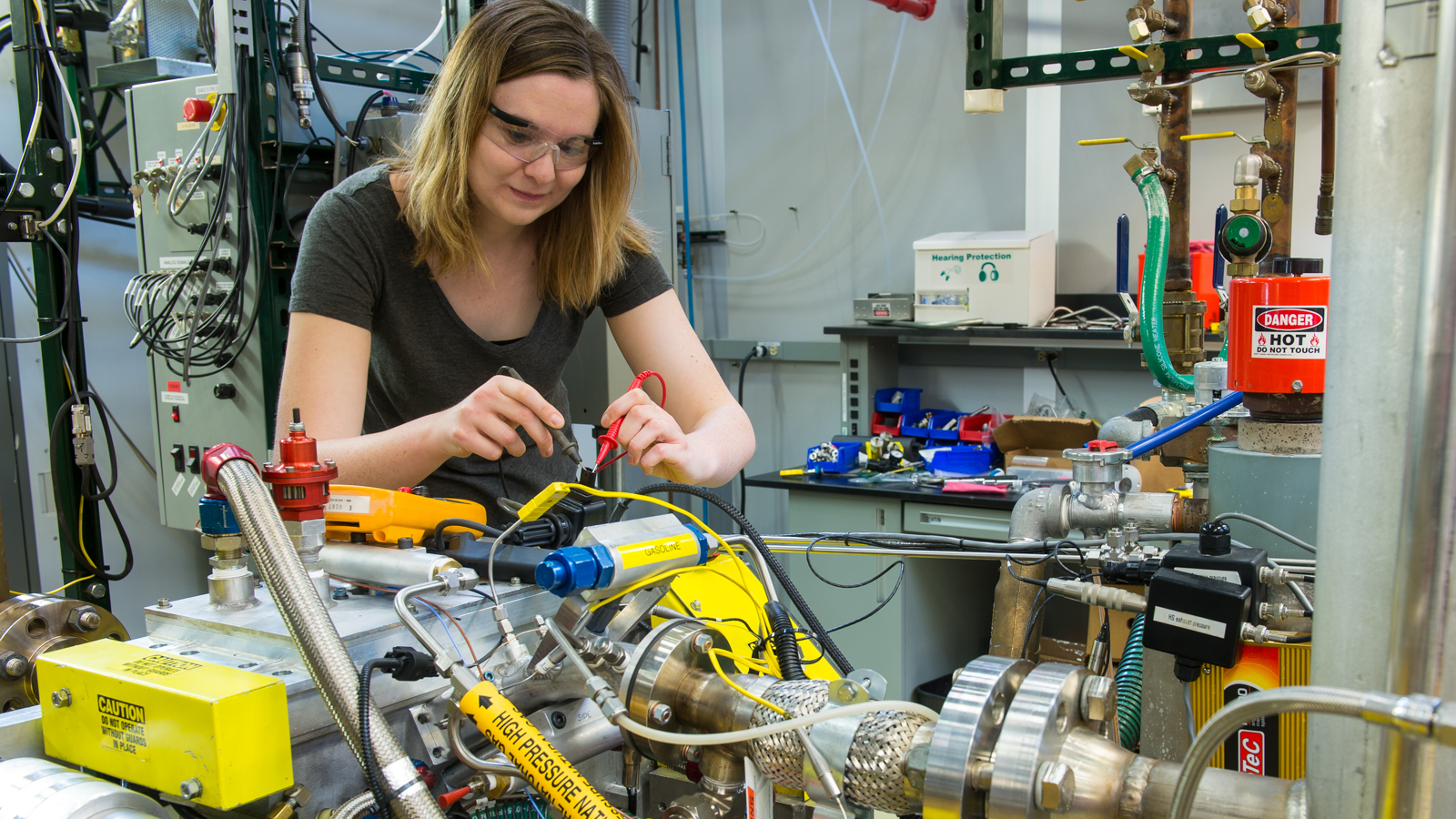 Visiting IIT Professor Carrie Hall troubleshoots the engine wiring harness. The Argonne system can replicate speed and load conditions found during typical vehicle operation for both naturally aspirated as well as turbocharged engines.
