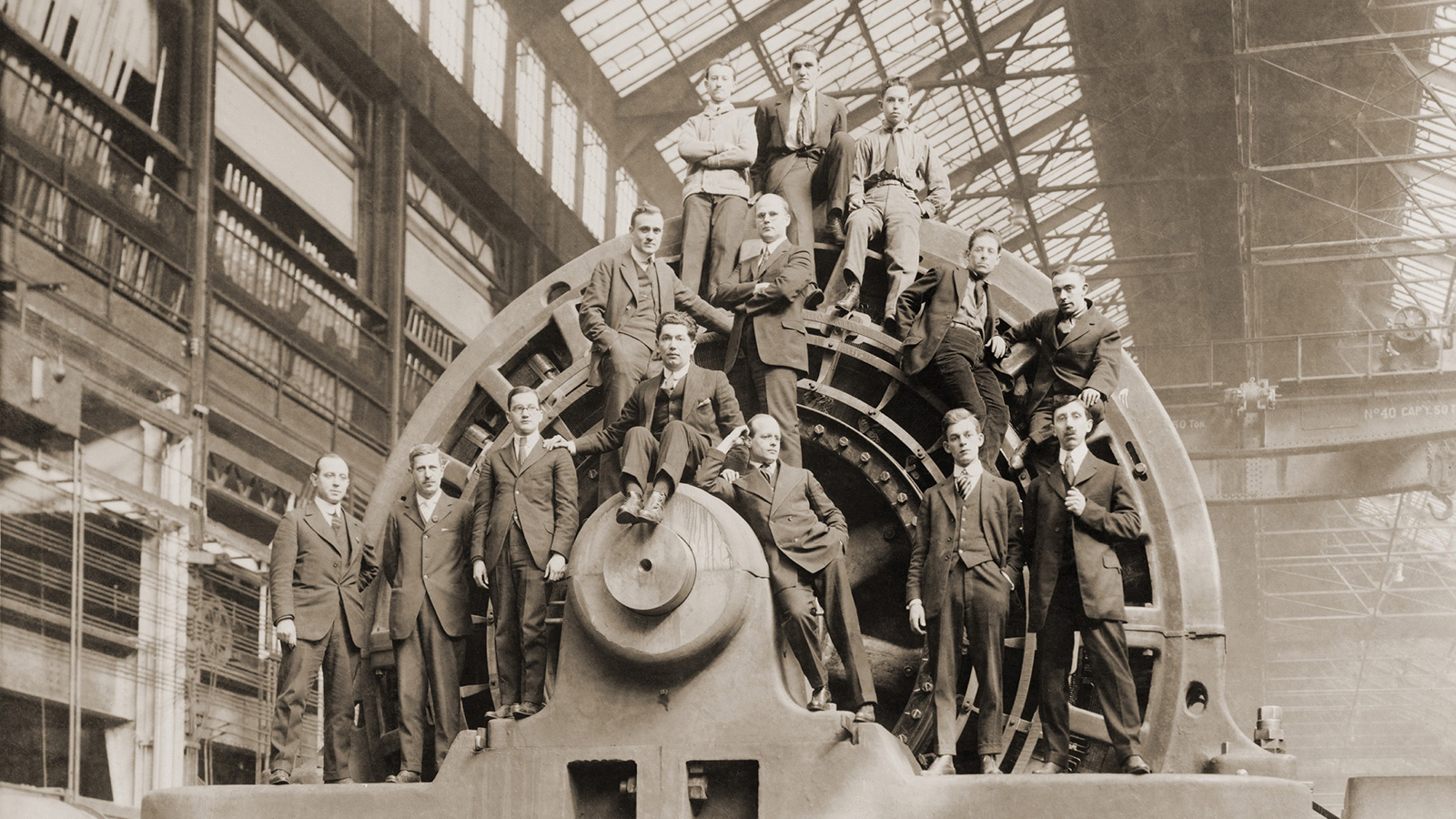 Sepia-toned photograph of massive electrical generator with 14 men standing and seated on it