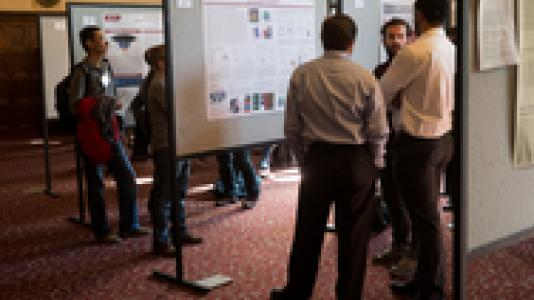Photograph of people looking at posters at a symposium.