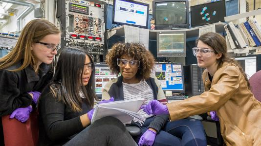Neuqua Valley High School students Anna Thomas, Vanessa Cai, Nadia Young and Natalie Ferguson discuss an experiment at Sector 20 of the Advanced Photon Source.