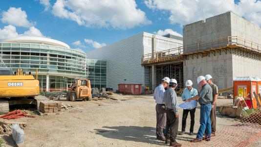 Building project managers and scientific leads confer at the site of a new clean room under construction at Argonne National Laboratory.