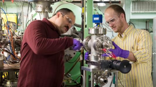 Argonne National Laboratory scientist Sergey Chemerisov (left) works with Ian Hamilton (right), CEO of Atlas Energy Systems and a member of Chain Reaction Innovation to set up a system to generate ionized gas from the Van de Graff Accelerator at Argonne.