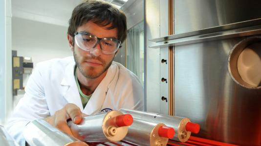 Panagiotis Prezas examines a battery cell in Argonne's Electrochemical Analysis and Diagnostics Lab