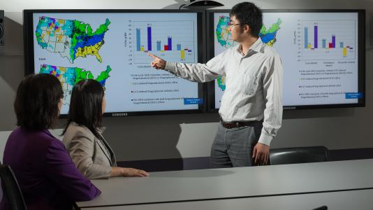 Argonne environmental analyst Hao Cai, environmental scientist Jiali Wang and climate scientist Yan Feng observe a U.S. map that plots the albedo effects observed across various agro-ecological zones.