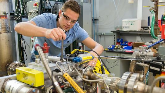 Argonne researcher Michael Pamminger installs a high-pressure natural gas feed line to the test system.