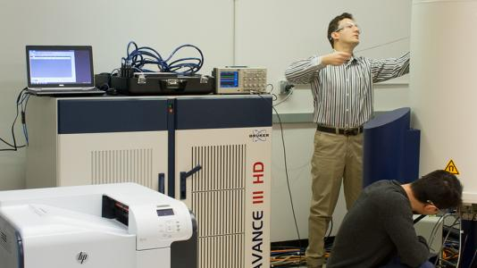 Baris Key, assistant chemist and Hao Wang, postdoctoral researcher prepare an experiment in Argonne's Nuclear Magnetic Resonance (NMR) laboratory.