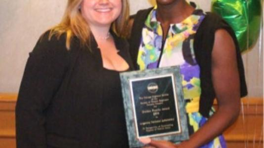 Argonne Gender Diversity Specialist Erin Thomas (right) accepted the 2014 Society of Women Engineers Golden Family Award on behalf of the laboratory at a recent SWE award presentation. SWE Chicago Regional Section President Jennifer Sciullo (left) presented the award.