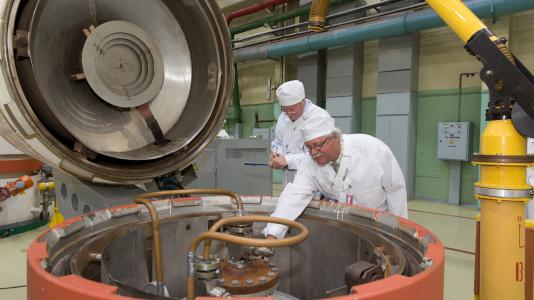 Greg Martin reads and Robert Elwood records the serial number of a vessel containing low-enriched uranium hexafluoride.