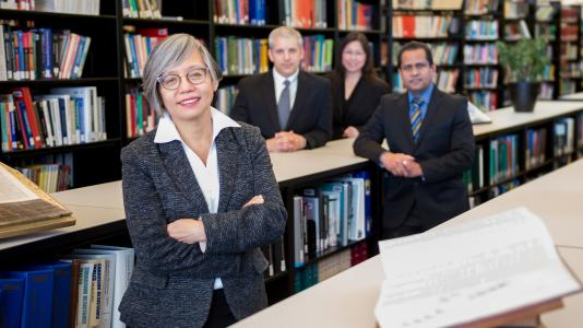 Linda Young, Argonne Distinguished Fellow in foreground and three other people in background of library setting.