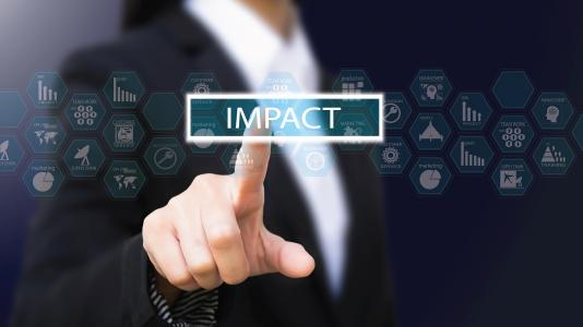 """Business woman pointing at the word """"IMPACT"""""""