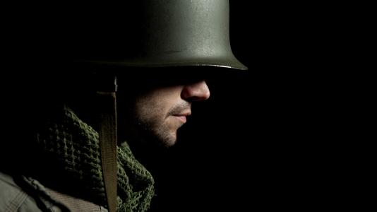 Side profile of soldier with green helmet and jacket