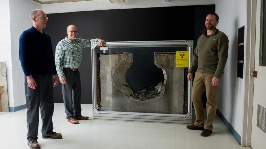 Nathan Bremer, Mitch Farmer (center) and Jeremy Licht (right) highlight a piece of concrete eroded in tests by corium — the lava-like material formed when uranium fuel rods in the reactor core melt, along with their protective metal cladding. The team's tests helped nuclear plant operators avoid $1 billion in expenses. Not shown: Stephen Lomperski and Dennis Kilsdonk. (Image by Argonne National Laboratory.)