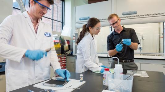 Argonne scientist Jason Croy, Manar Ishwait, and Michael Murphy assemble lithium-ion battery electrodes for testing. (Image by Marke Lopez / Argonne National Laboratory.)