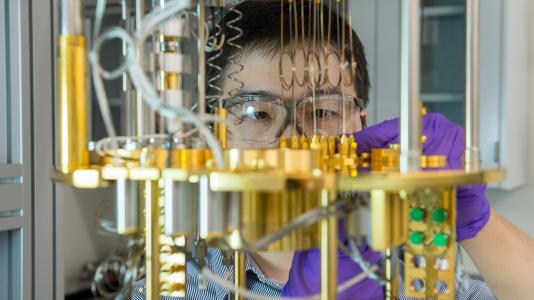 Capabilities at the Quantum Matter and Devices laboratory at Argonne's Center for Nanoscale Materials, a U.S. Department of Energy Office of Science User Facility, aid in development of quantum materials and devices. Here, Argonne scientist Dafei Jin observes a dilution refrigerator, a cryogenic cooling device for materials used for quantum computing. (Image by Mark Lopez / Argonne National Laboratory.)