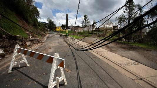 Barricade blocking road that has powerlines down. (Image by Shutterstock / RaiPhoto.)