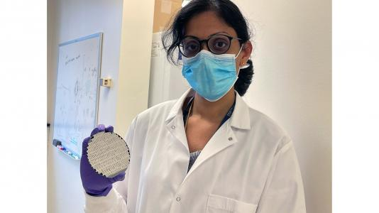 Scientist holding round object. (Image by Nidhi Sharma, The University of Chicago.)