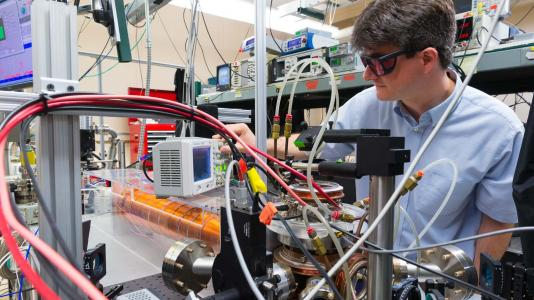 Scientist wearing goggles, using equipment. (Image by Argonne National Laboratory.)
