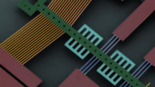 A false-color image of a microelectromechanical device. The diamond-based actuator is colored gold.
