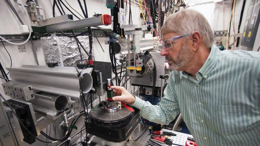 Prof. Stuart Stock (Northwestern University) in the X-ray Science Division beamline 2-BM research station at the Advanced Photon Source (APS), readying a sample of shark spine for imaging using the high-brightness X-rays from the APS. (Image by Argonne National Laboratory.)