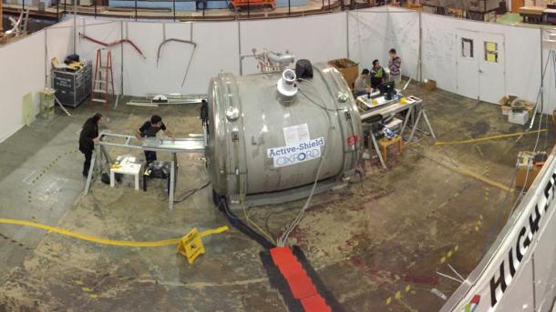 Panorama view of the 4 Tesla solenoid facility with Midhat Farooq and Joe Grange aligning an NMR calibration setup (left of the magnet), Ran Hong and students improving the calibration motion control system (right of the magnet) and David Flay analyzing current NMR calibration data. (Image by Argonne National Laboratory.)