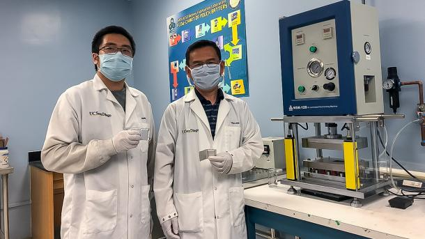 UC San Diego researchers Haodong Liu and Ping Liu hold batteries made with the disordered rocksalt anode material they discovered, standing in front of a device used to fabricate battery pouch cells. (Image by University of California San Diego.)