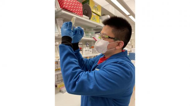 Masked researcher in lab. (Image by Kevin Zhao.)